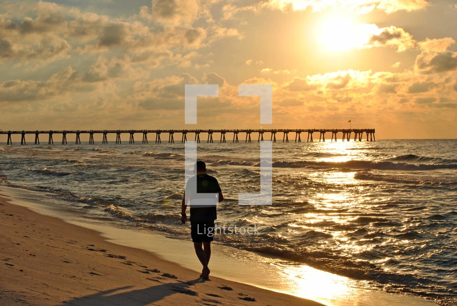 A beachcomber enjoys the solitude at daybreak near the fishing pier on Pensacola Beach, Florida.
