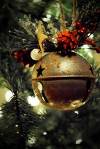 Large jingle bell ornament on Christmas tree.