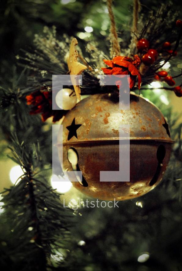Large jingle bell ornament on Christmas tree.