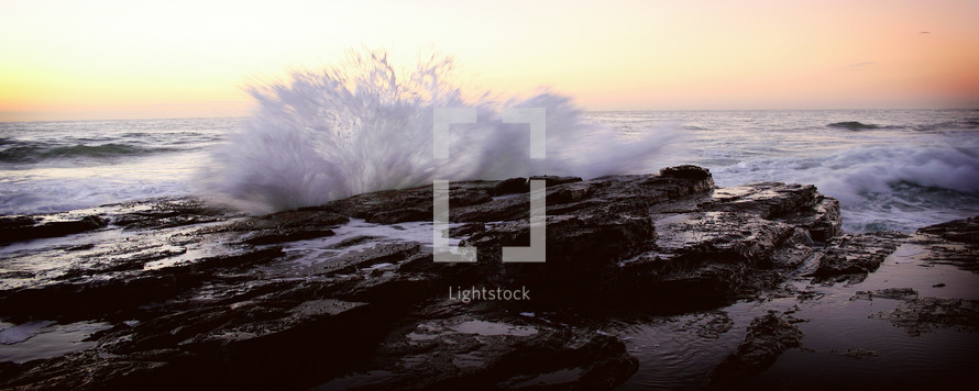 powerful waves crashing into rocks on a shore