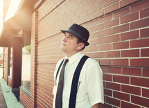 a man in a hat and suspenders looking up