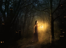 woman carrying a lantern in a dark forest