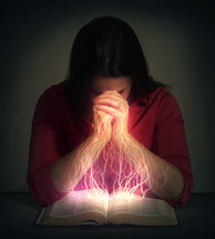 synapses sparking as a woman reads a Bible