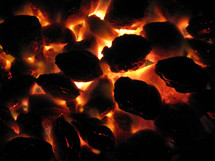 Glowing coals of a charcoal fire.