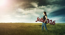 Woman carrying a sign of John 3:16 in a field