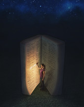 woman shining a flashlight on the pages of a giant Bible