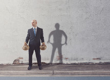constrast, man standing holding bags of cash and shadow with empty pockets