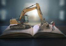 bulldozer digging into a Bible