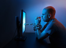 man chained to his computer