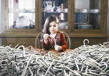 surreal image of a little girl painting hundreds of candy canes red.