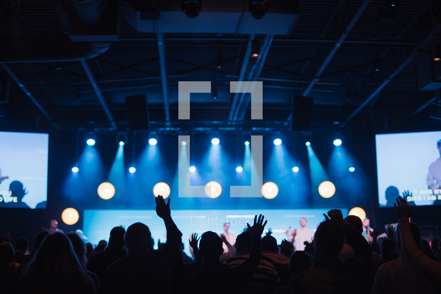 audience with raised hands at a contemporary worship service,