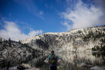 man with a backpack standing in front of a lake and snow covered mountains
