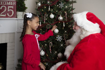 a child and Santa decorating a Christmas tree