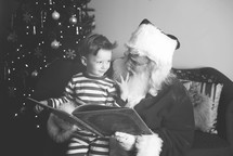 Santa and a boy reading a book together
