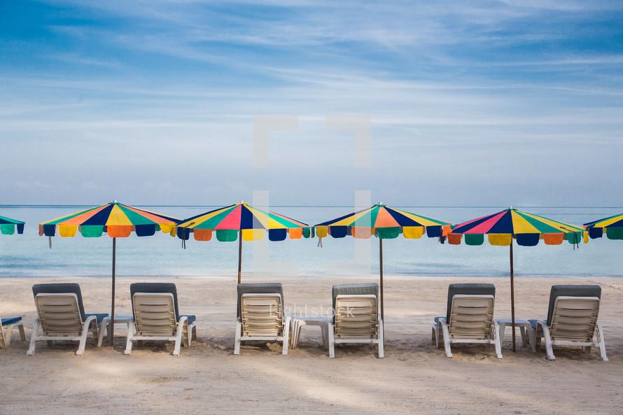 lounge chairs and beach umbrellas on a beach