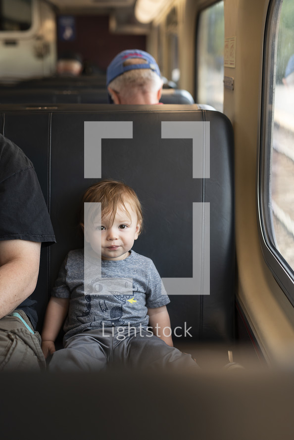 toddler boy in a train seat