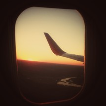 The wing of a plane out a plane window.