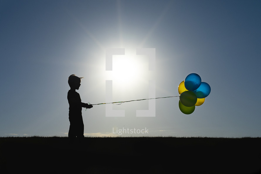 silhouette of a child holding balloons