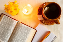 opened Bible, pen, notepad, candle, and tea