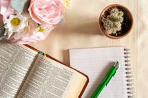 opened Bible, pen, notepad, flowers, and potted cactus