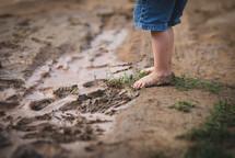 child's bare feet standing in mud