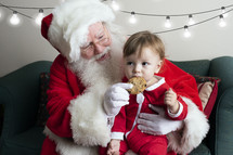 a toddler eating a cookie on Santa's lap