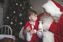 a toddler with cookies and milk on Santa's lap