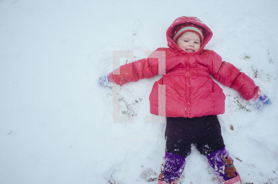 toddler making a snow angel