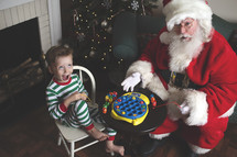 a child playing with toys with Santa