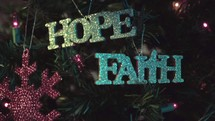 """Hanging """"hope"""" ornament on Christmas tree next to """"faith"""" ornament"""