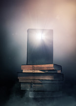 man climbing a stack of books with glowing Bible on top