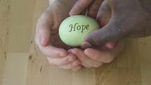 cupped hands holding an egg with the word hope on it