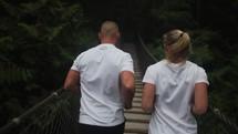 joggers on a swinging bridge