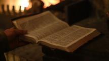 man reading a Bible fireside
