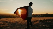 Boy with a superman cape standing outdoors  Imagination | Dreaming | Destiny | Vision| Heroes | Justice | Kids Ministry | Movies | Heroes | Bravery | Brave | Courage | Courageous | Strong | Strength | Stand | Determination | Persevere | Sermon Series | Motion | Camera Movement | Evening | Golden Hour