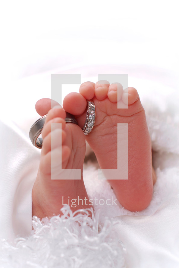 infant's feet with wedding bands around the toes