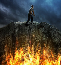 man in chains on a cliff above the flames of hell