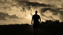 silhouette of a man walking and an electrical storm behind him