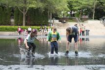 children splashing in a puddle