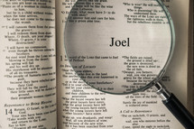 magnifying glass over Bible - Joel
