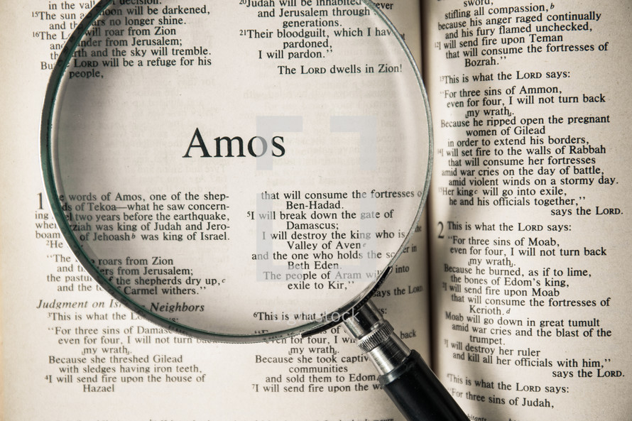 magnifying glass over Bible - Amos