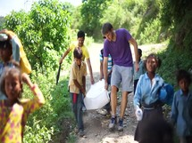 school children carrying supplies down a dirt road in Nepal