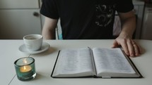 man sitting down to read a Bible with coffee