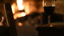person holding a Bible fireside with a glass of wine