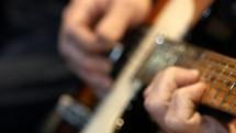 a man stemming a guitar