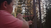 Young boy shooting a slingshot in the forest. - 1 of 2