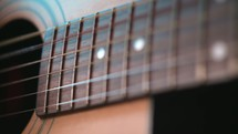 close-up of the strings of a guitar as a man plays