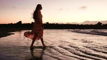 a woman in a flowing dress walking towards the ocean