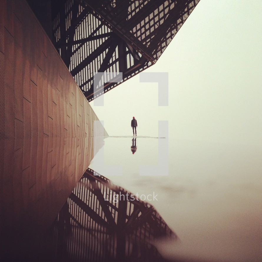 man standing on water covered street