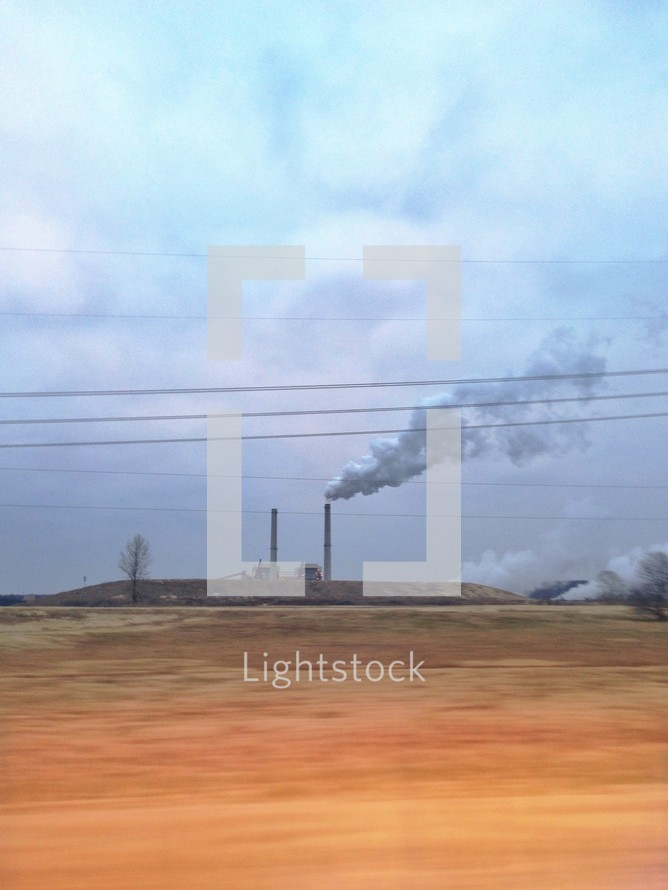smoke from a distant factory across a field